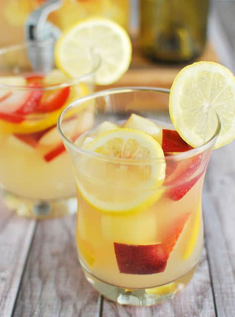 Pineapple Lemonade Sangria by Fake Ginger - Nothing screams summer more than frosty fruity drinks. Wine slushies, mules, sangria,  mimosas, cocktails, margaritas, and more! Graduations, Memorial Day, Fourth of July, or just a summer gathering with friends and family are all great reasons to throw a summer party.  No summer party is complete without fruity, slushy, cold drinks. You'll love these 10 summer drink recipes.  You'll be happy you tried them all. #summerdrinks #summerdrinkrecipes #foodanddrink #frozendrinks #wineslushies #frozencocktails #cocktails #partydrinks #partydrinkrecipes #HWS #healthywealthyskinny